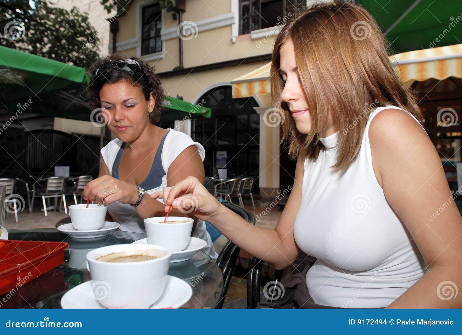 Amis féminins appréciant une cuvette de coffe