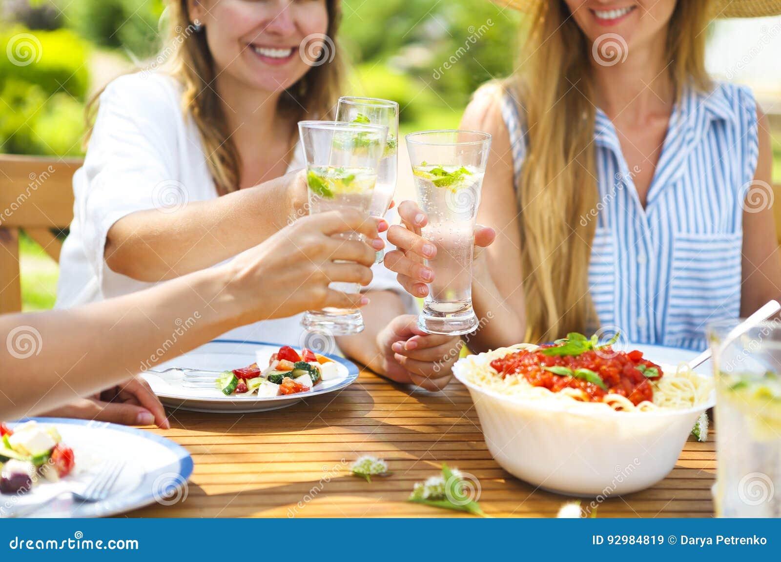 Amis féminins heureux avec des verres de limonade à la table de salle à manger dedans