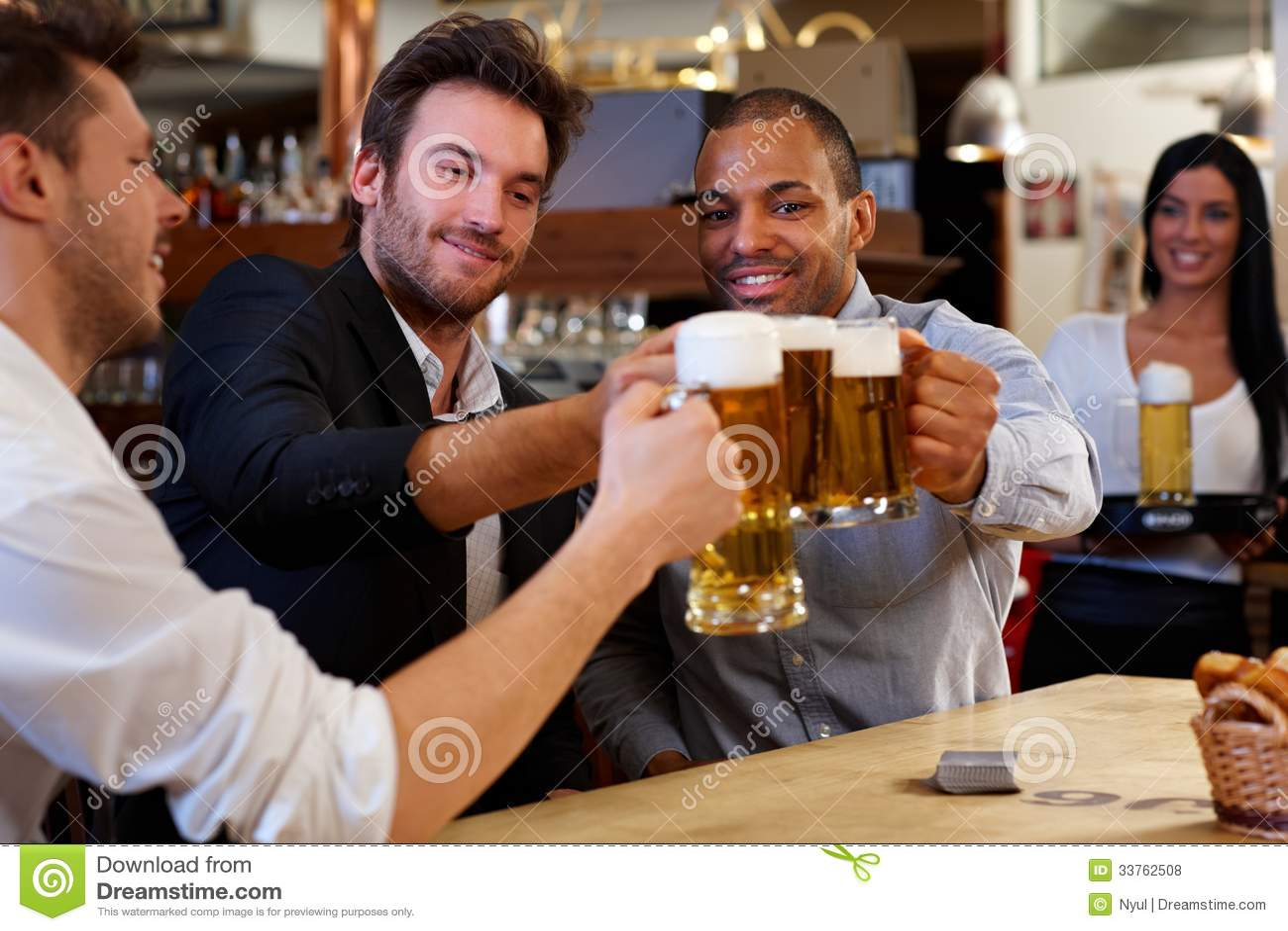 Amis faisant tinter avec des tasses de bière dans le bar