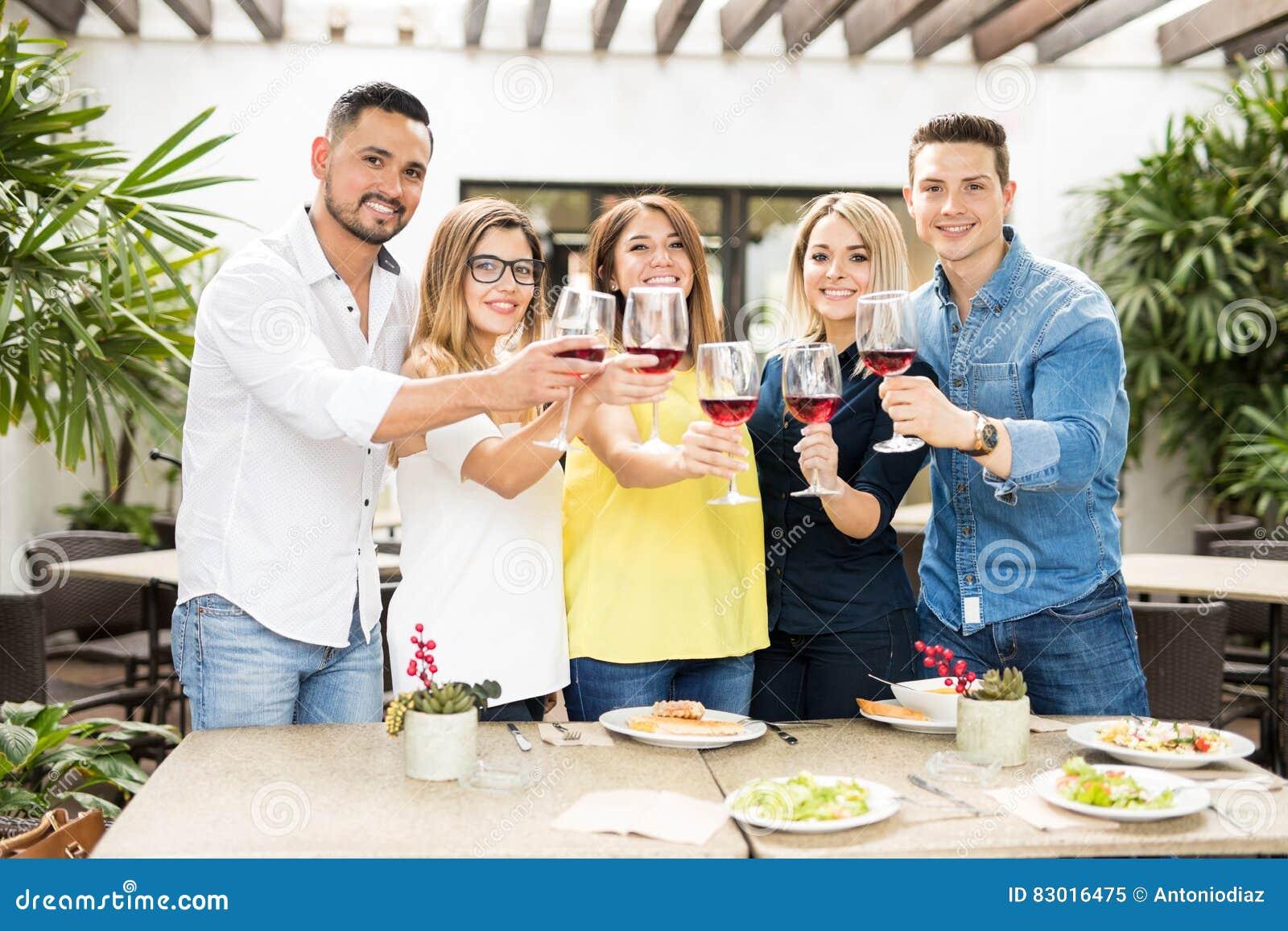 Amis faisant un pain grillé avec du vin