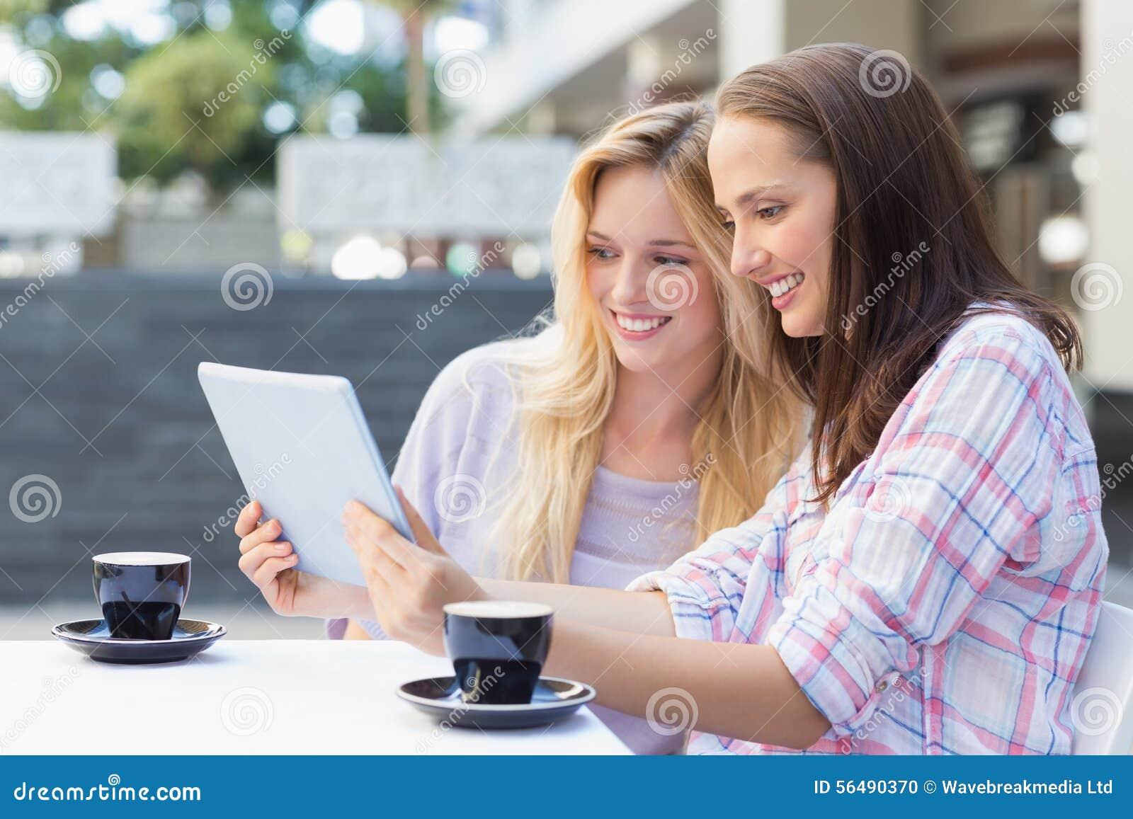Amis heureux de femmes regardant le comprimé