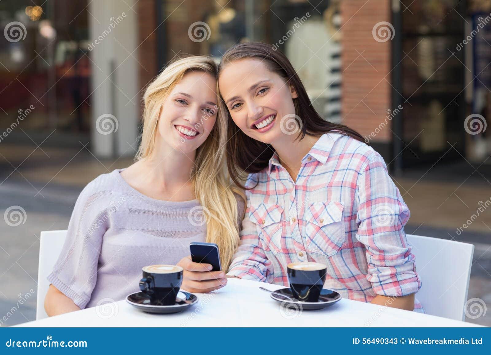 Amis heureux de femmes souriant à l appareil-photo