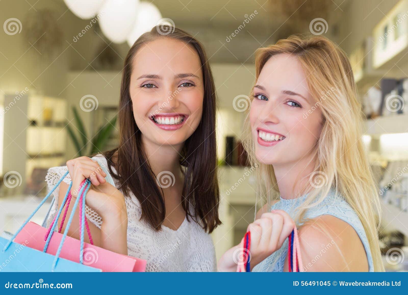 Amis heureux de femmes souriant à l appareil-photo avec des paniers