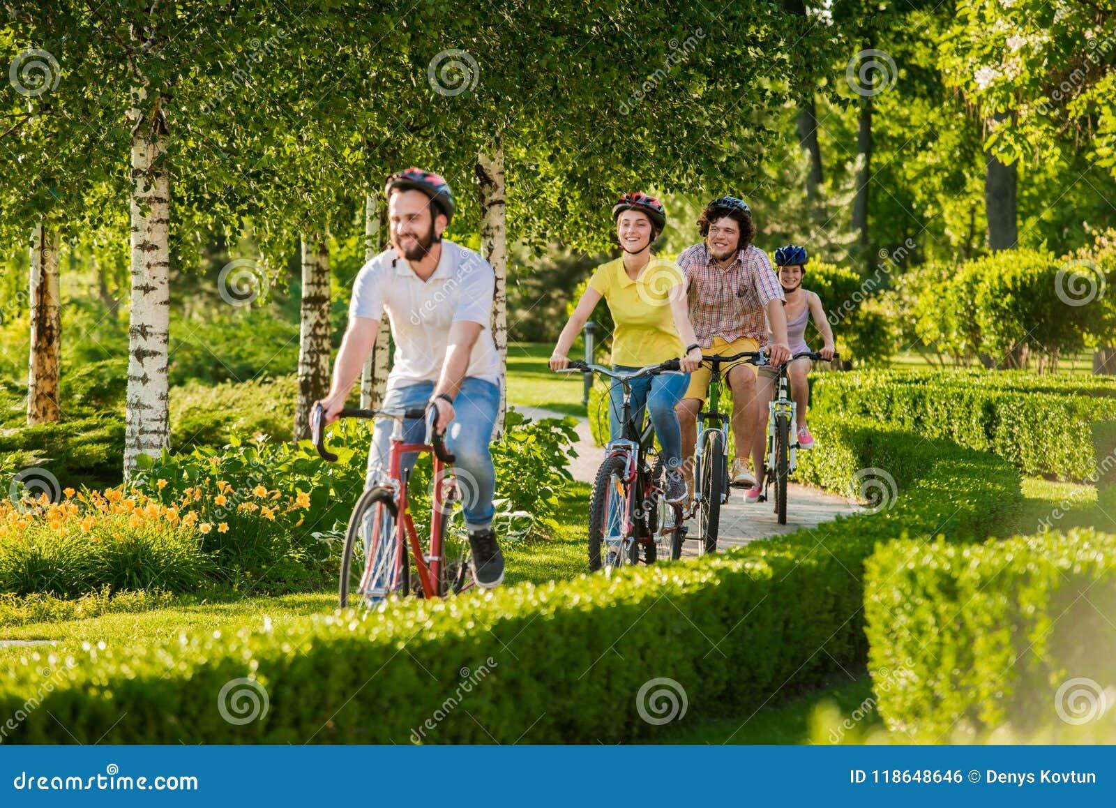 Amis heureux faisant un cycle en parc de ville