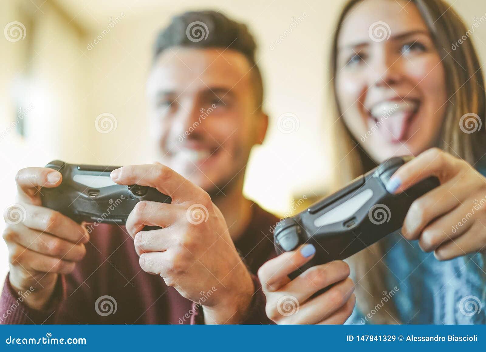 Amis heureux jouant des jeux vidéo en leur appartement - jeunes couples hilares ayant l amusement avec la nouvelle technologie de