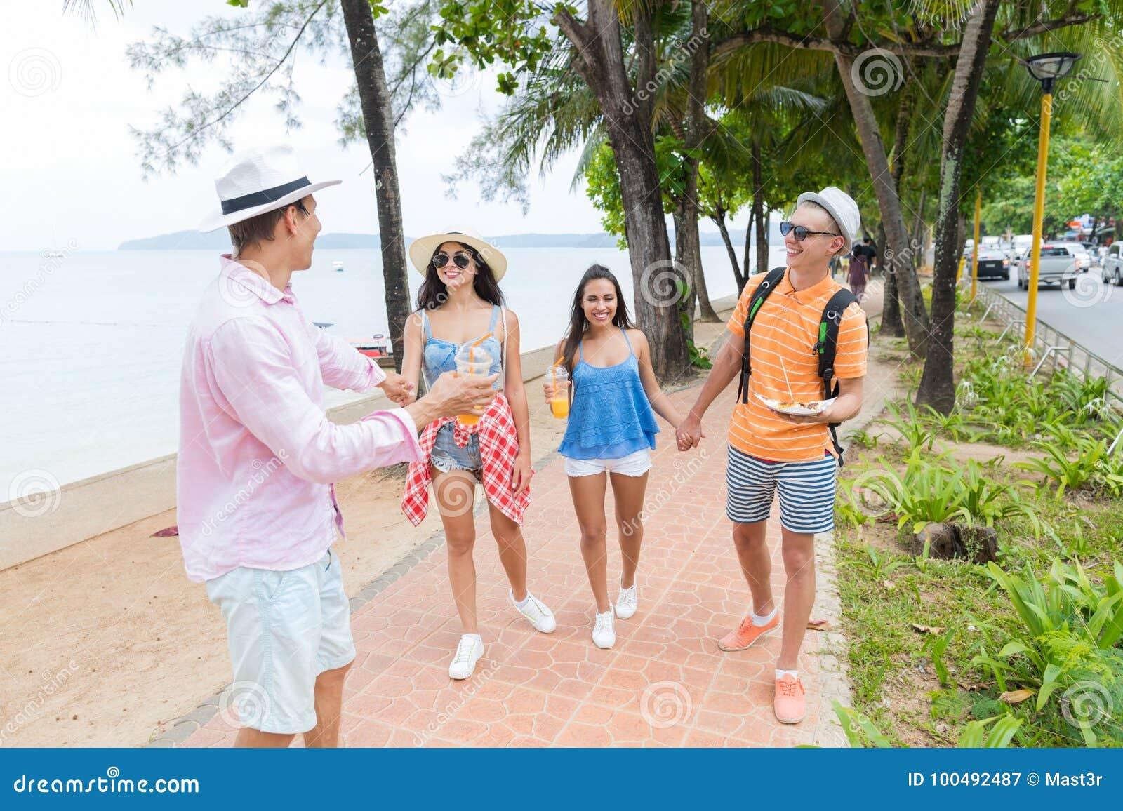 Amis heureux marchant ensemble en parc près du jeune groupe de personnes de mer sur des vacances et la communication de touristes