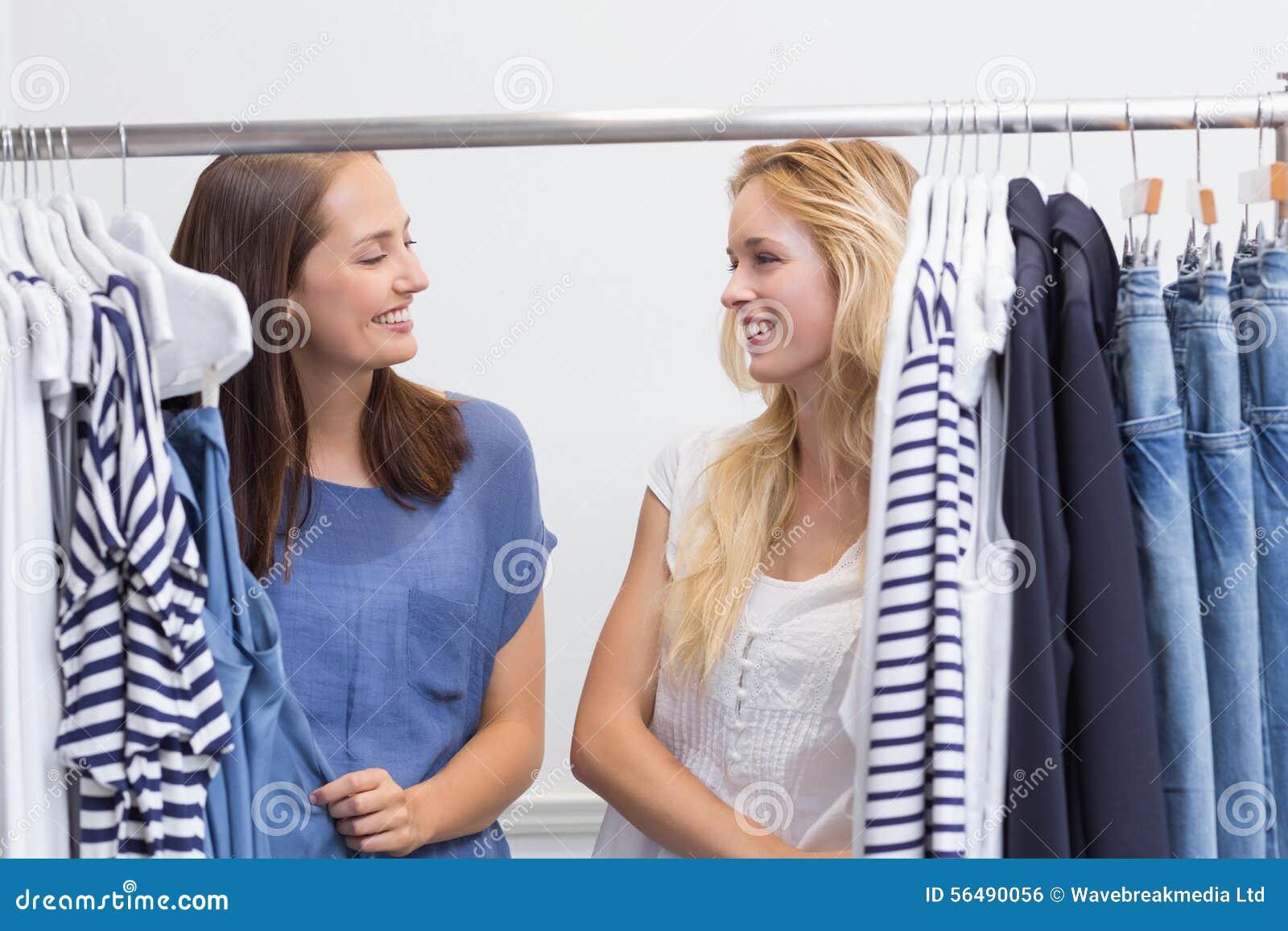 Amis heureux passant en revue dans le support de vêtements