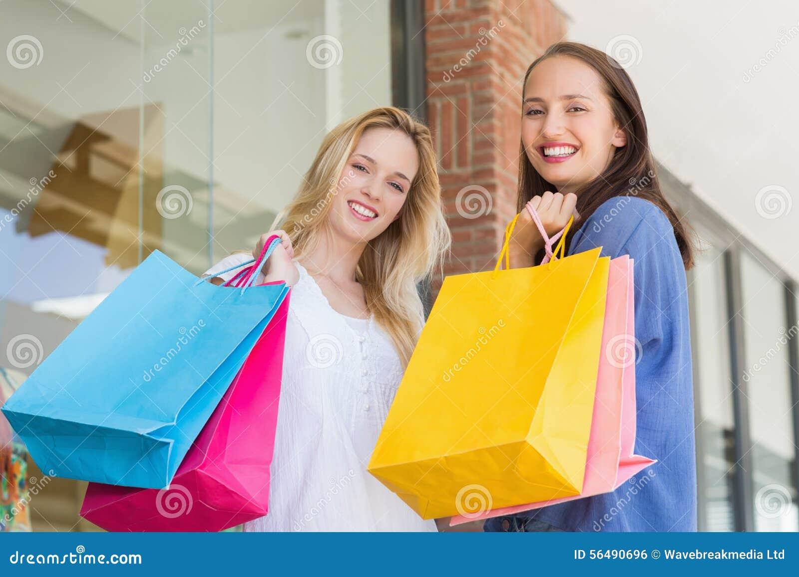 Amis heureux retenant des sacs à provisions