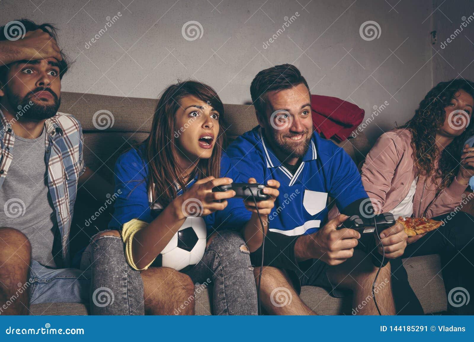 Amis jouant un jeu vidéo du football
