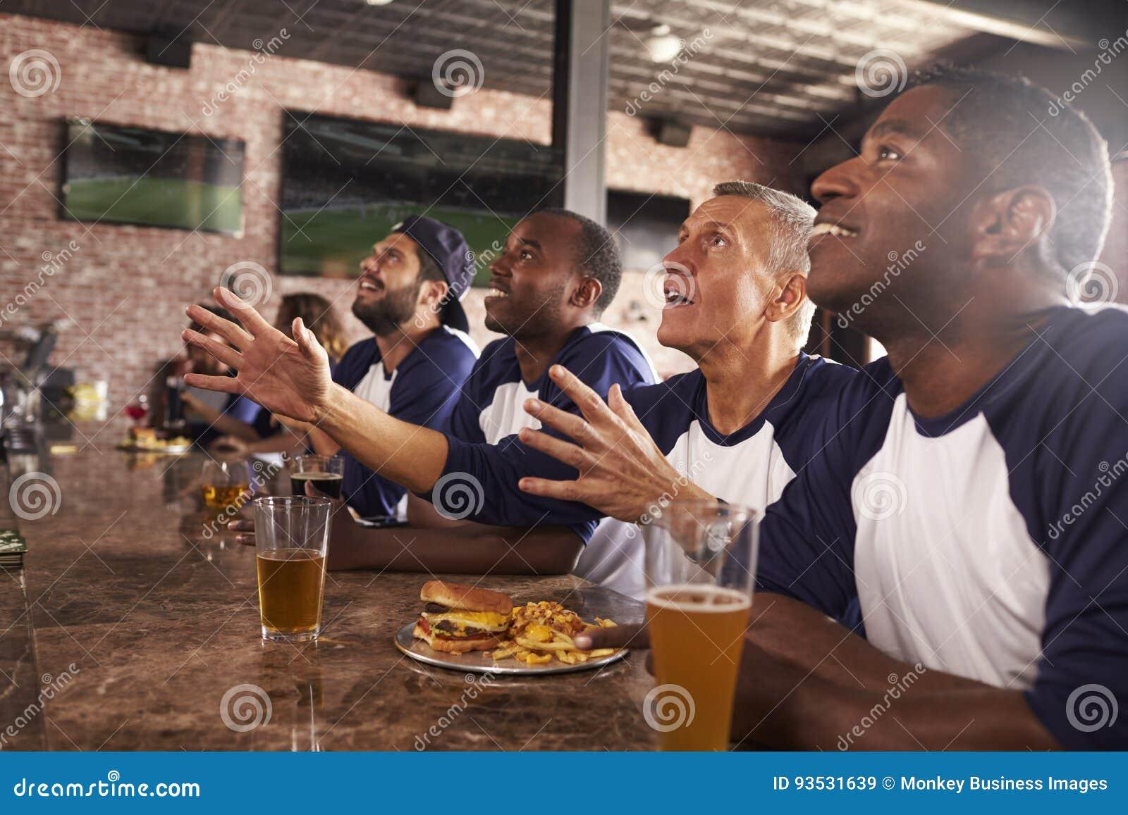 Amis masculins au compteur dans le jeu de observation de barre de sports