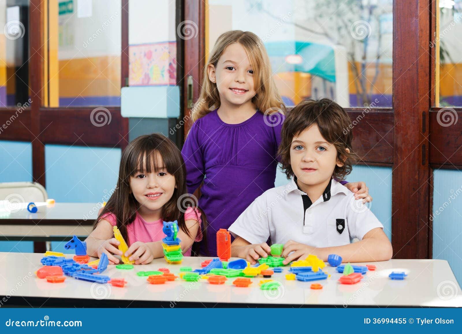 Amis mignons avec des blocs sur le bureau dans la salle de classe