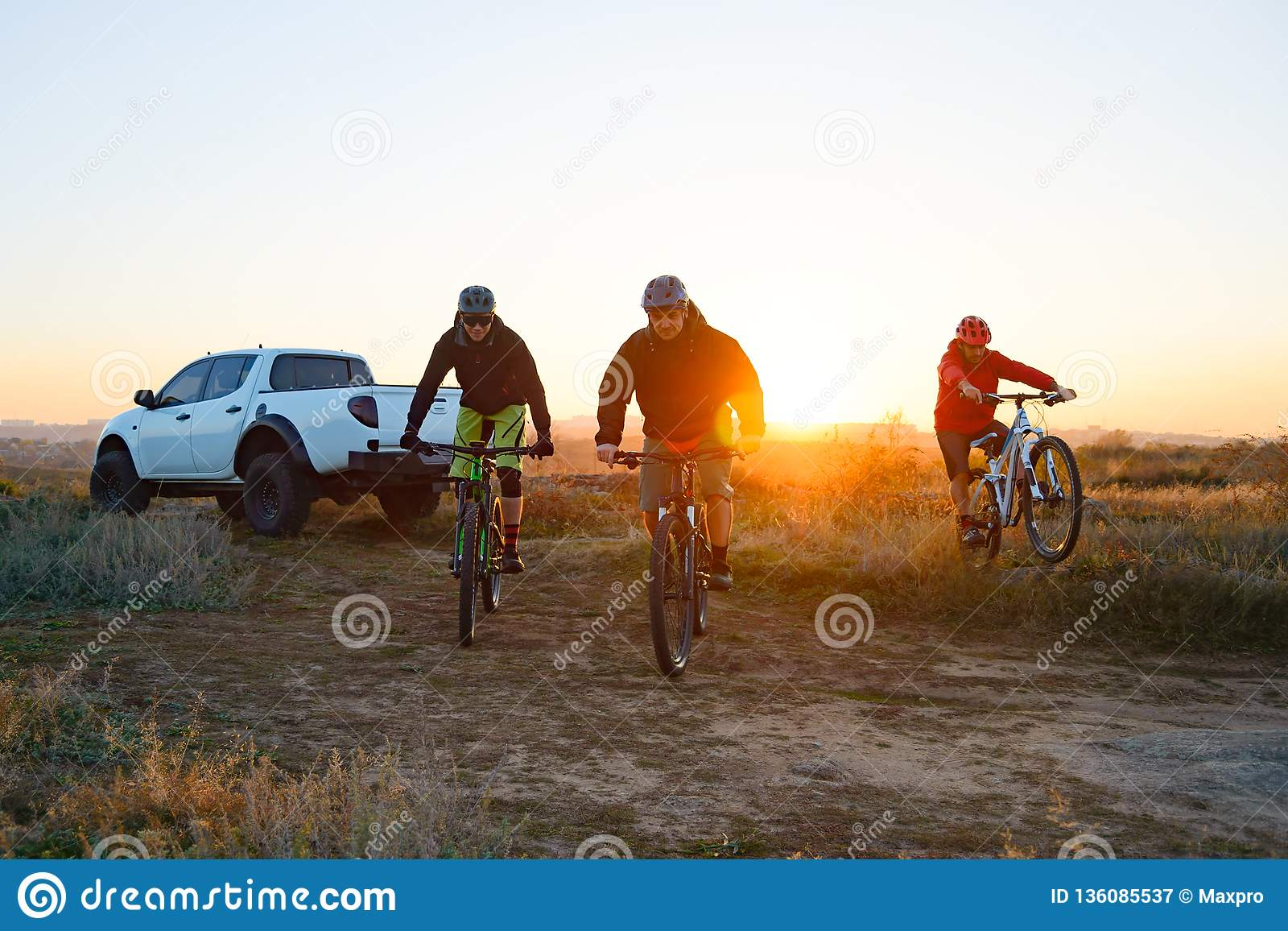 Amis montant des vélos dans les montagnes devant le camion d Off Road de collecte au coucher du soleil Concept d aventure et de v