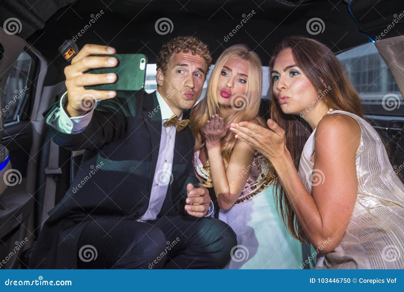 Amis prenant un selfie derrière une limousine