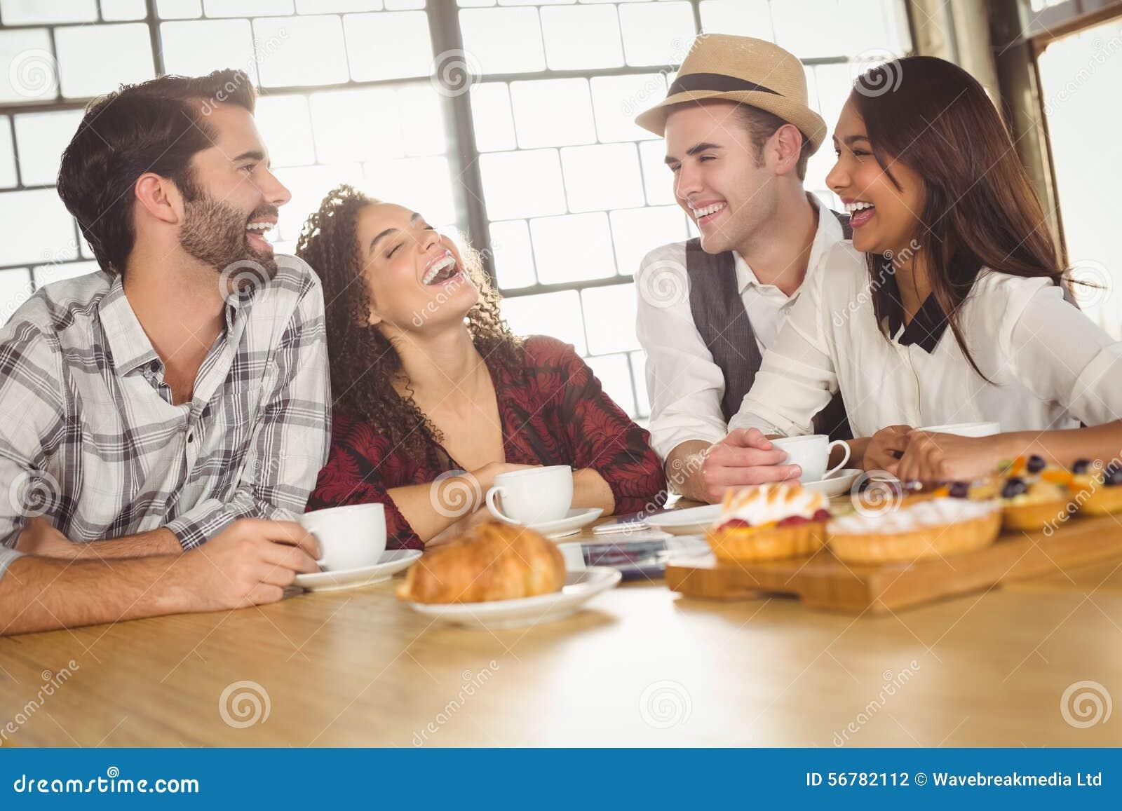 Amis riants appréciant le café et des festins