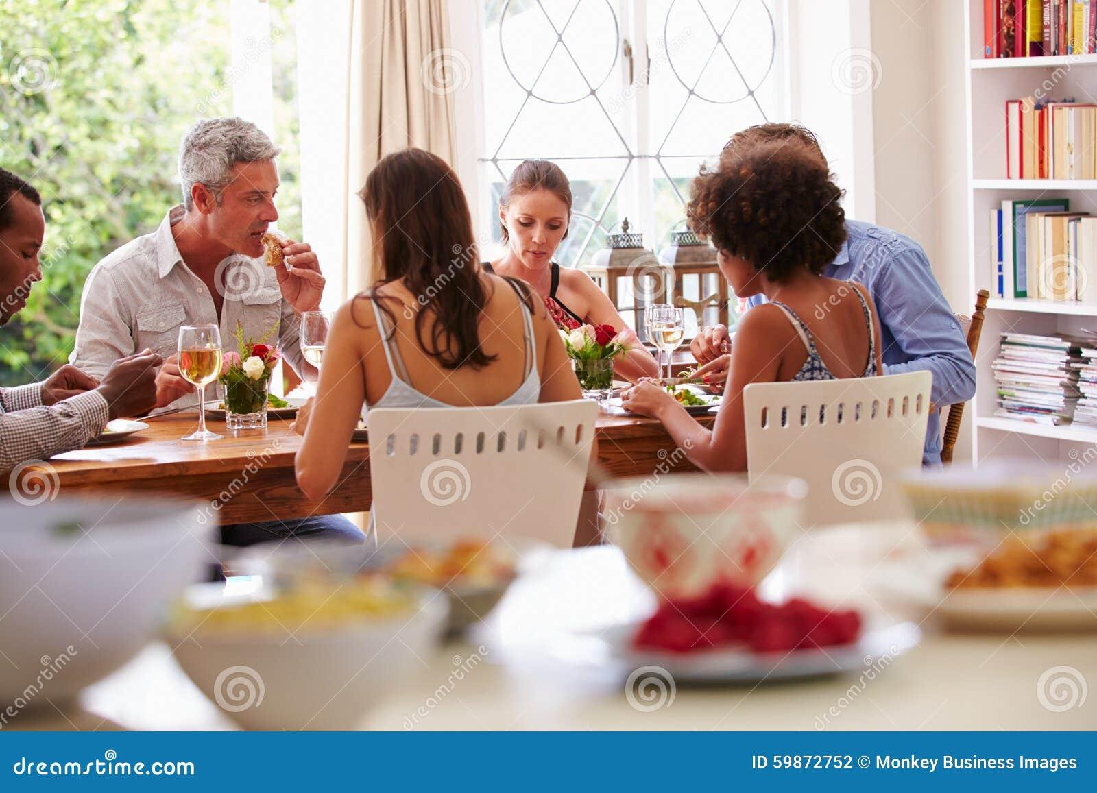 Amis s asseyant à une table parlant pendant un dîner