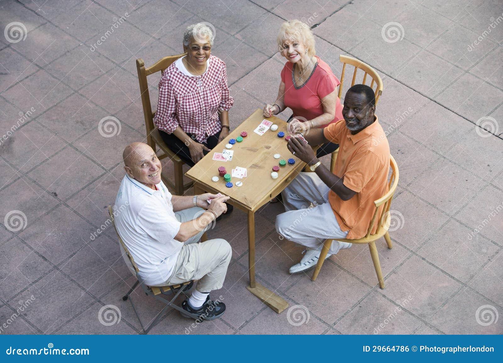 Amis supérieurs heureux jouant des cartes