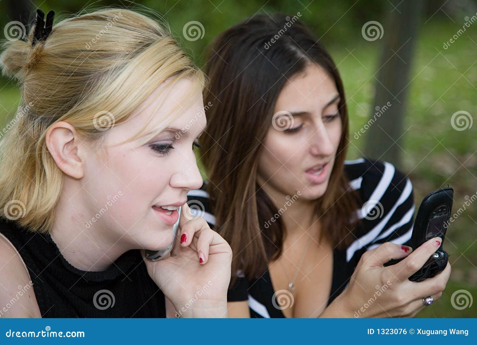 Amis sur le téléphone portable ensemble (belle jeune blonde et Brune