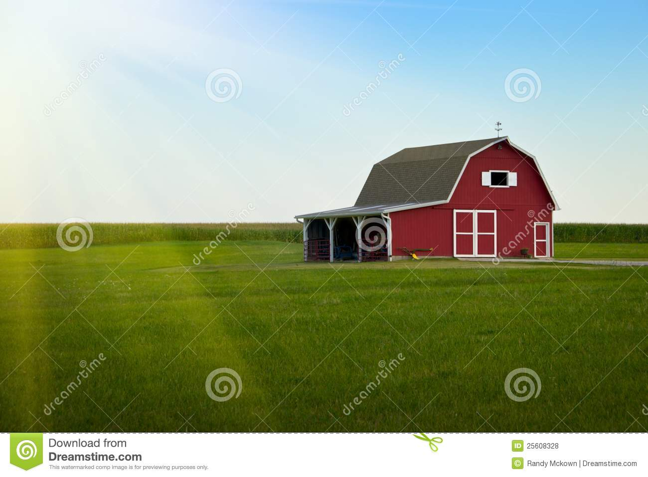 Red barn on an Amish farm in green field with blue sky and sunrise ...
