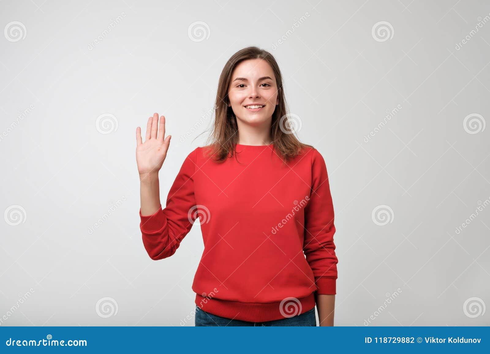 Amistoso-mirando al adolescente europeo se vistió en pulover rojo que decía el hola, agitando su mano