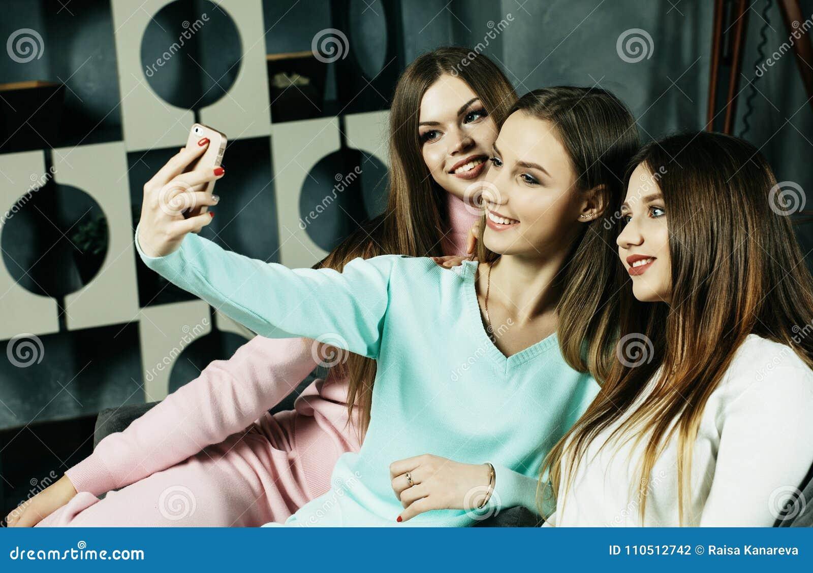 Amizade, povos e conceito da tecnologia - amigos ou adolescentes felizes com o smartphone que toma o selfie em casa