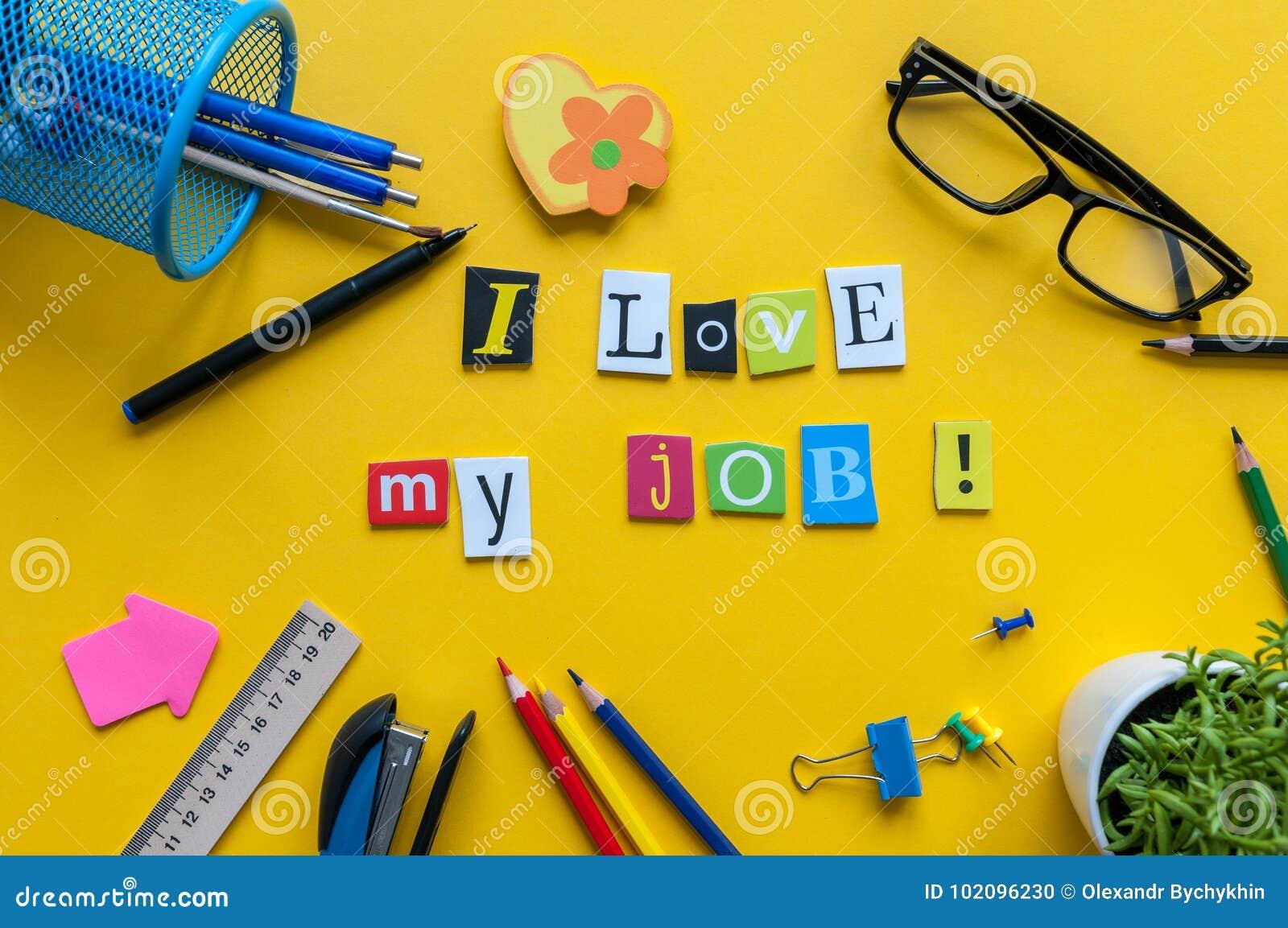 Amo mi palabra del trabajo escrita por las letras talladas en espacio de trabajo casero amarillo con los materiales de oficina
