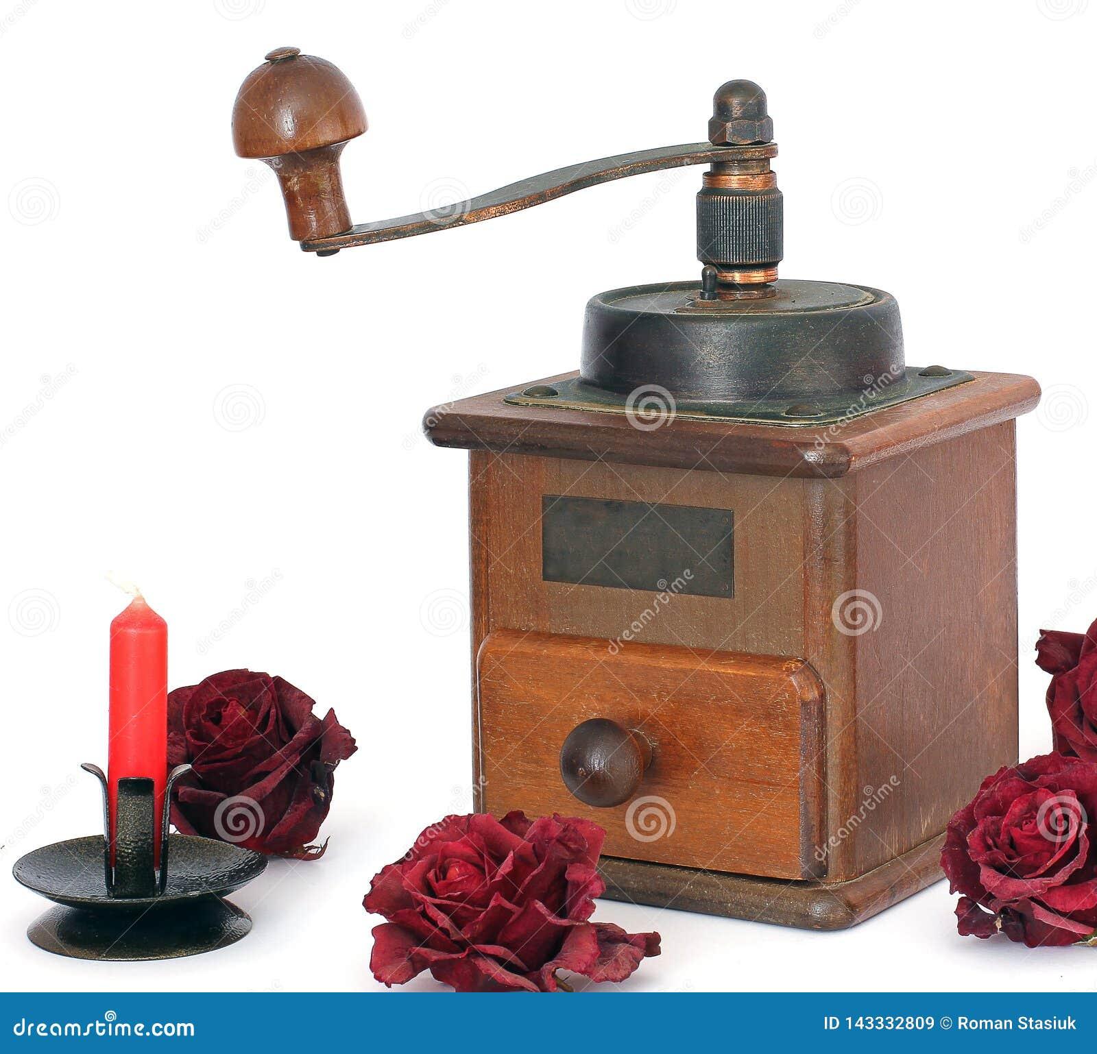 Amoladora de café manual con las rosas en un fondo blanco antiquary