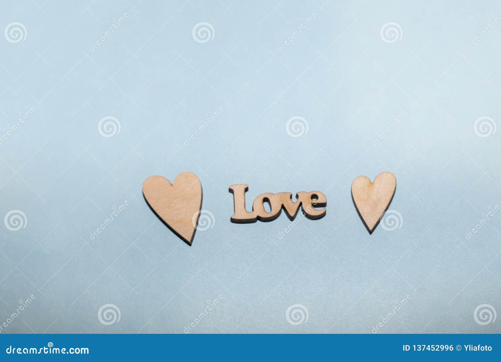 Amor da palavra de uma árvore em um claro - fundo azul Dois corações de madeira inscription
