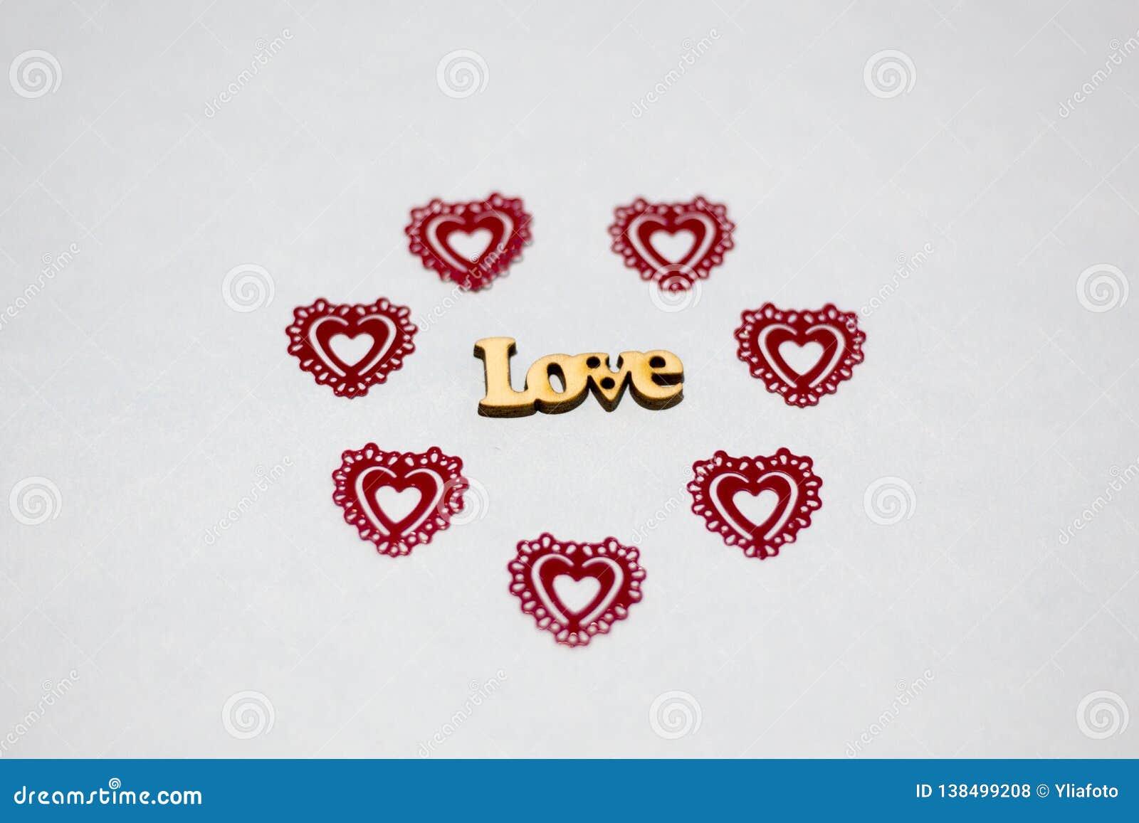 Amor da palavra em um ambiente de corações vermelhos Inscrição de madeira Plástico a céu aberto dos corações