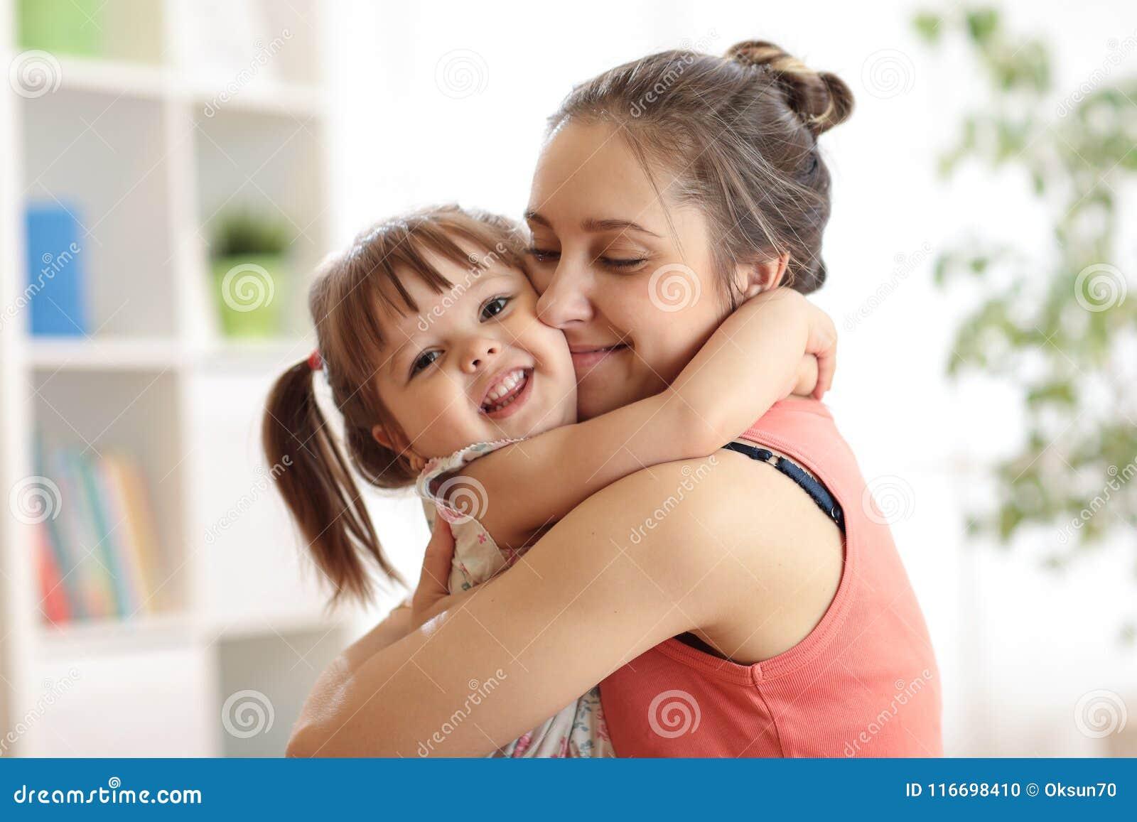 Amor e conceito dos povos da família - filha feliz da mãe e da criança que abraça em casa
