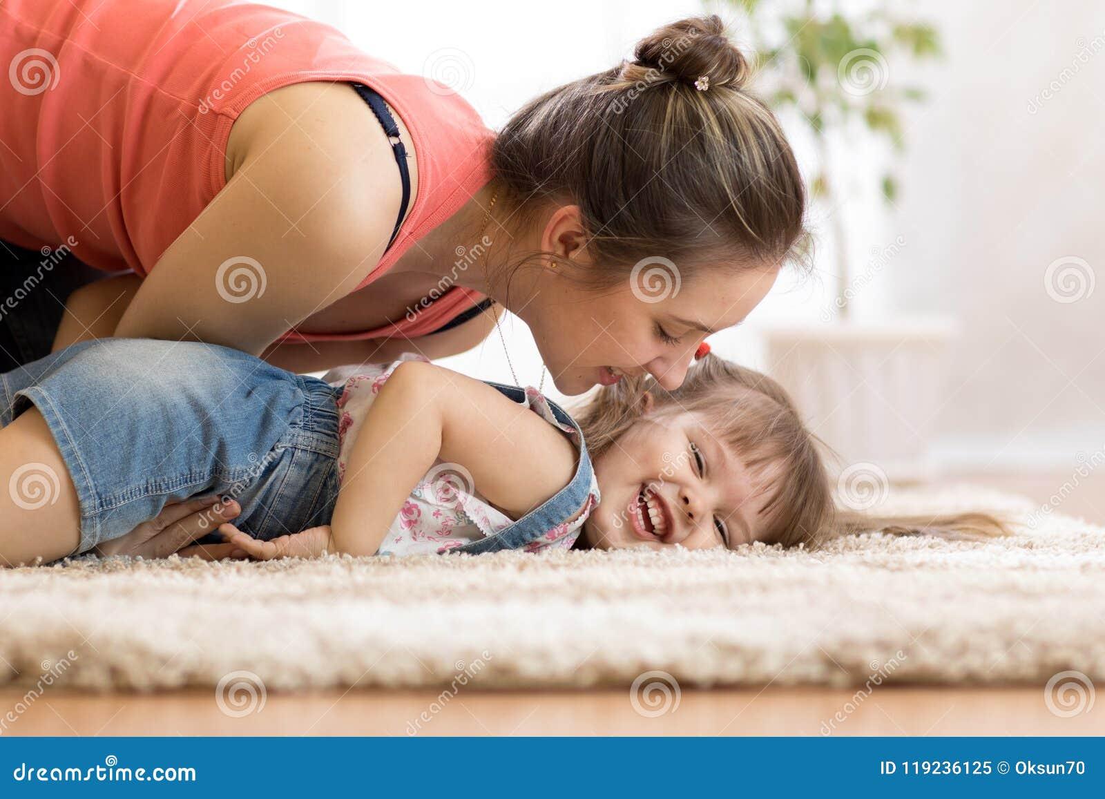 Amor e conceito dos povos da família - filha feliz da mamã e da criança que tem um divertimento em casa