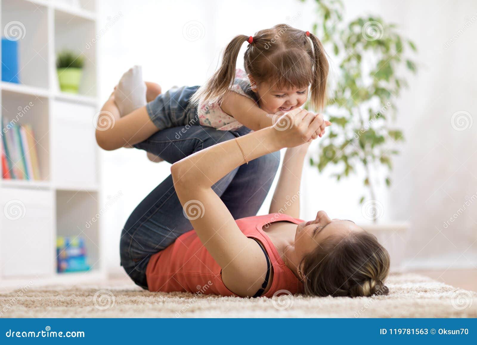 Amor y concepto de la gente de la familia - hija feliz de la mamá y del niño que se divierte en casa