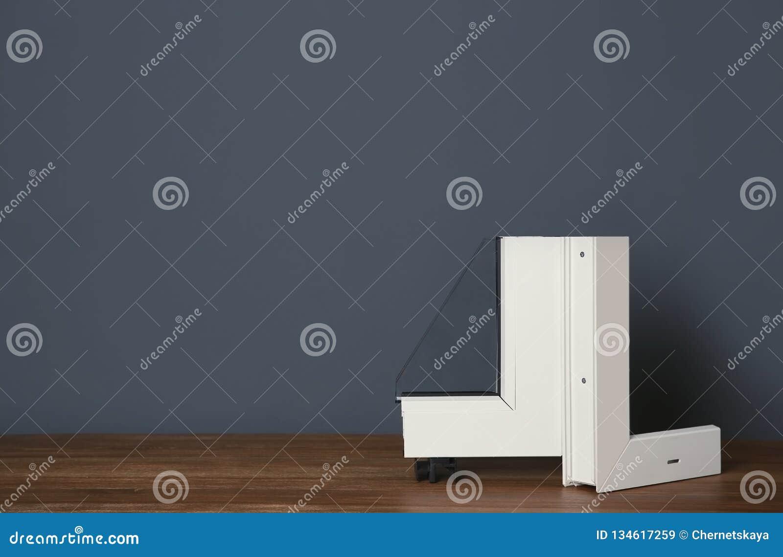 Amostra de perfil moderno da janela na tabela contra a parede cinzenta