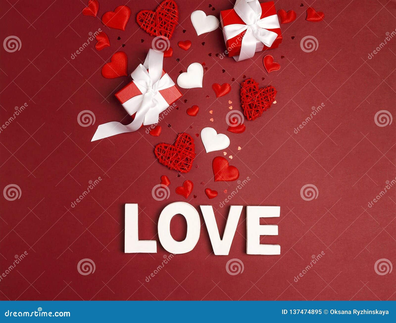 Amour de mot de fond de jour de valentines de St, cadeaux et coeurs décoratifs sur le rouge