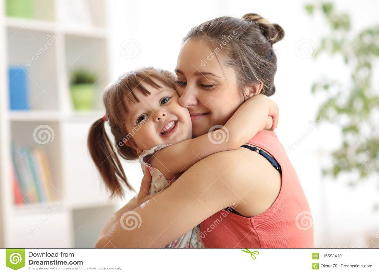 Amour et concept de personnes de famille - fille heureuse de mère et d enfant étreignant à la maison
