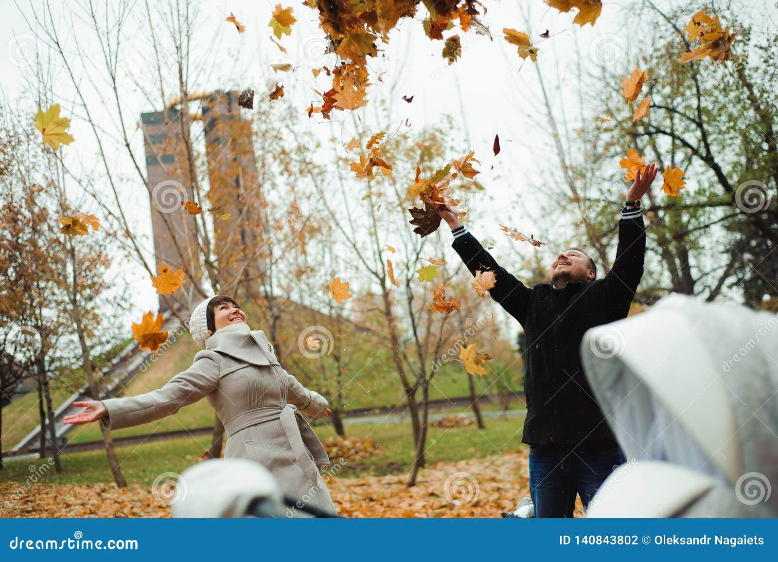 Amour, relations, saison et concept de personnes - feuilles d automne de lancement de jeunes couples heureux en parc