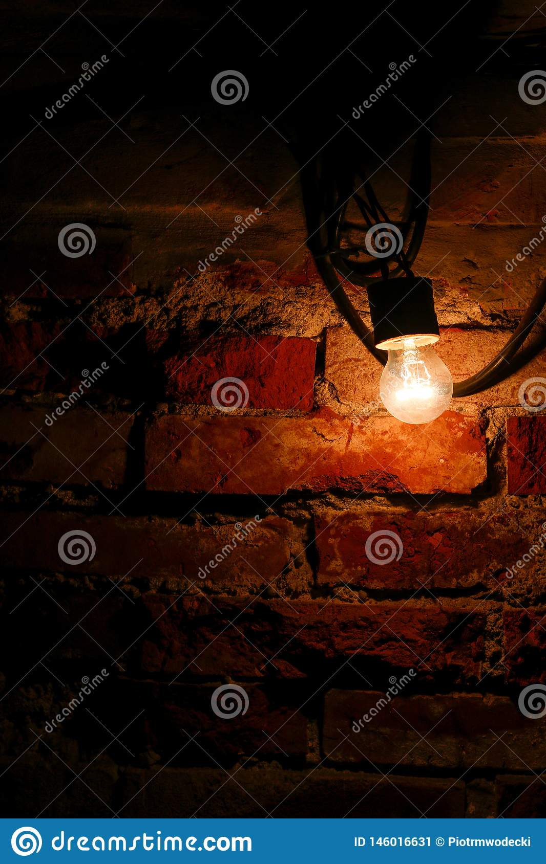 Ampola brilhante ao lado de uma parede de tijolo velha