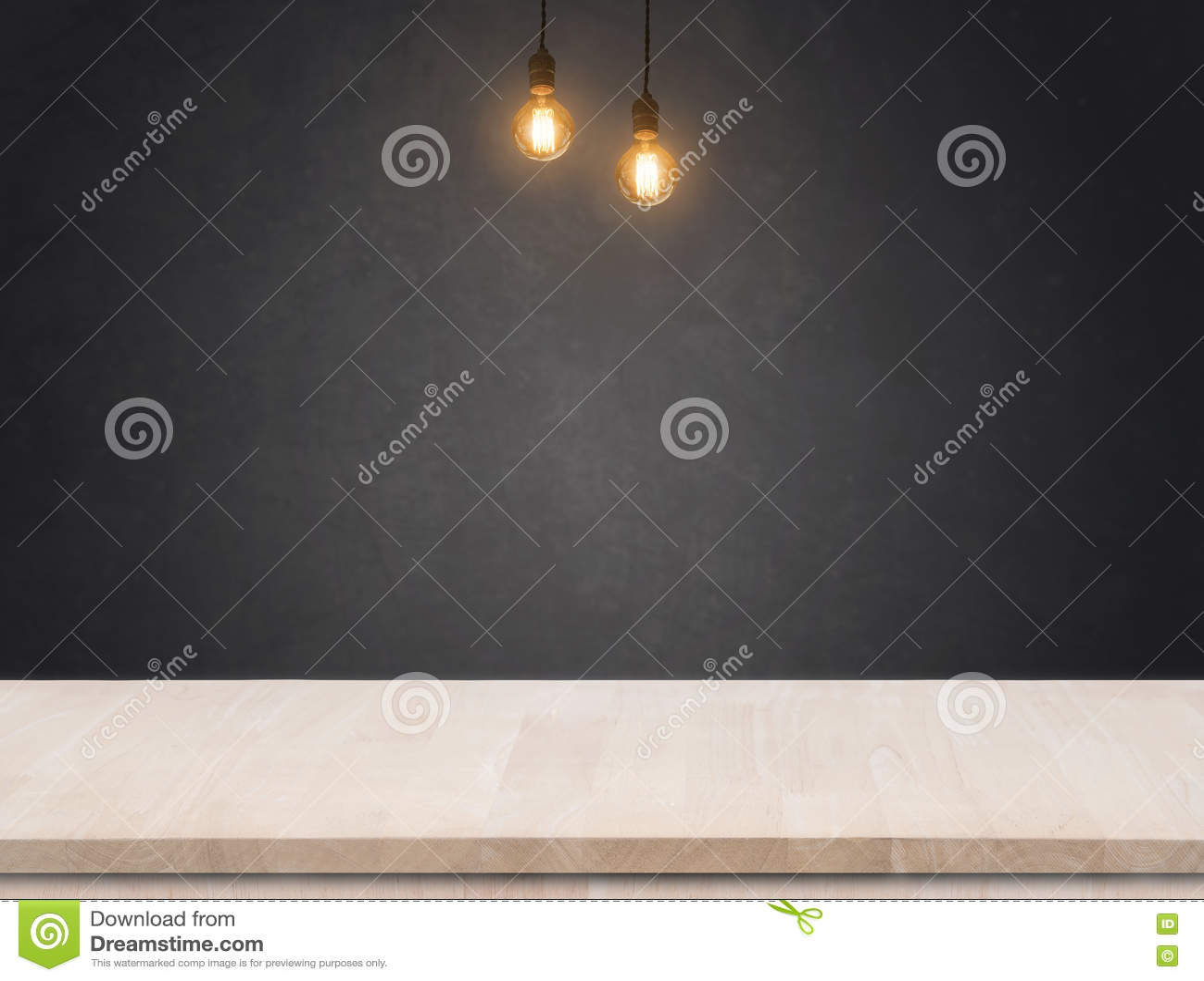 Ampola do tungstênio com fundo da parede do cimento e a tabela pretos da madeira
