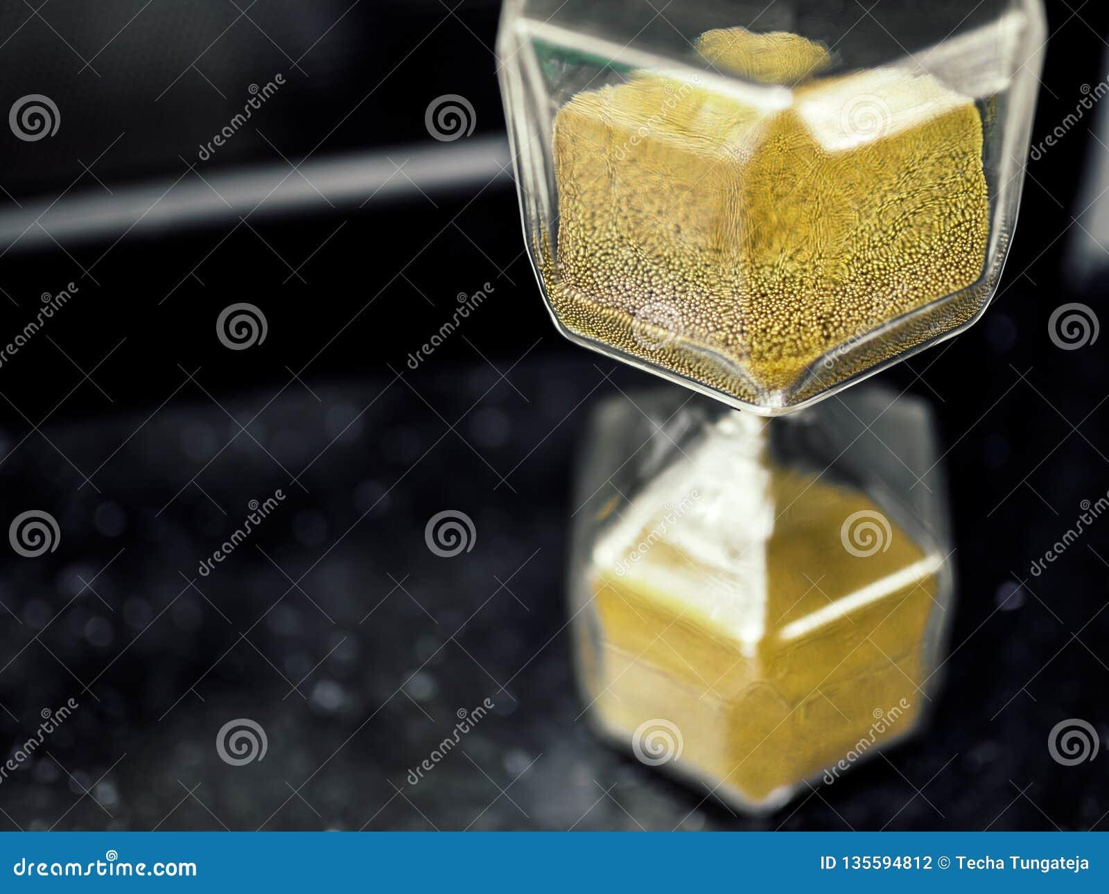 Ampulheta moderna do hexágono com a semente dourada da areia
