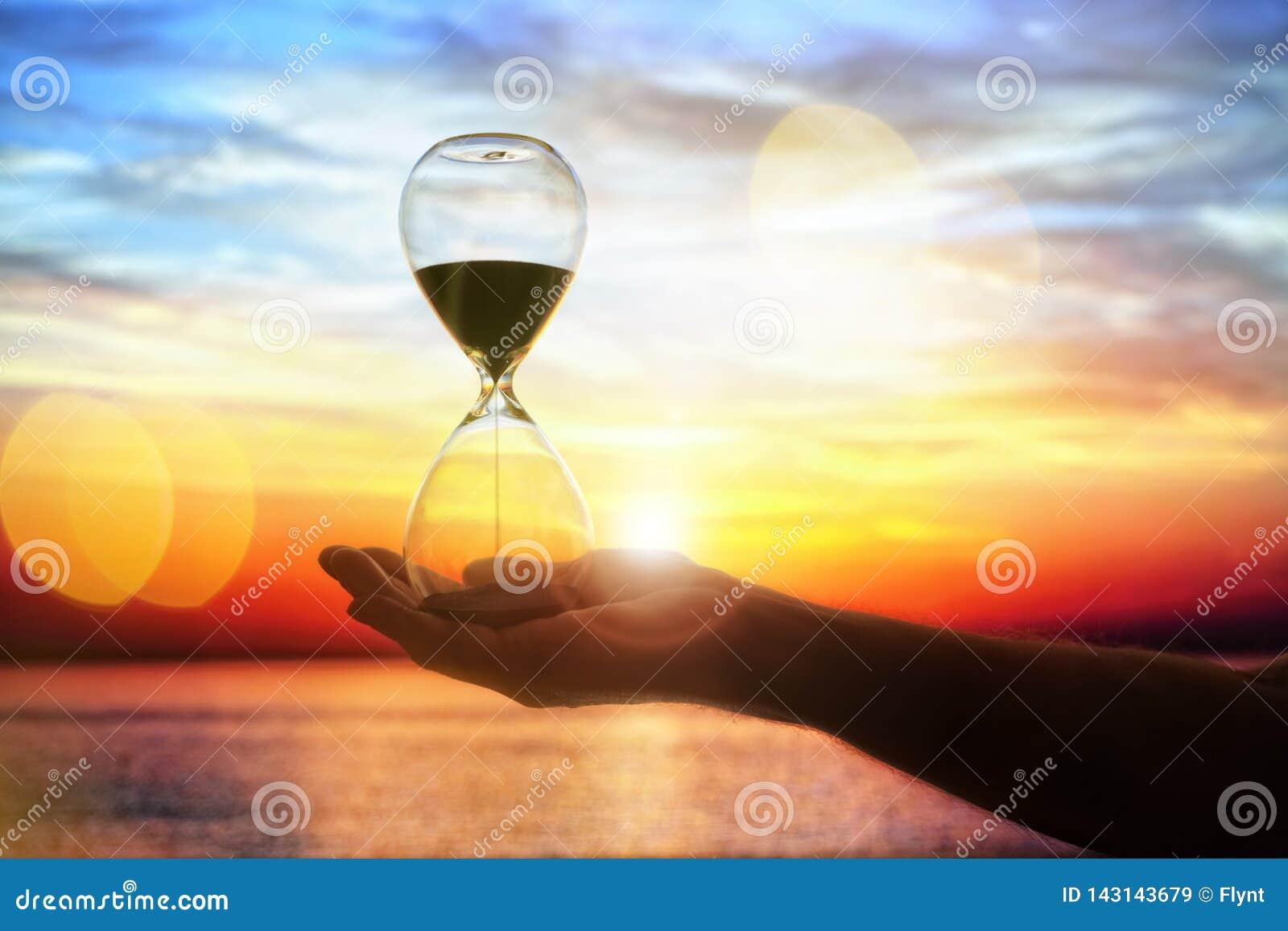 Ampulheta no conceito do por do sol para a passagem do tempo