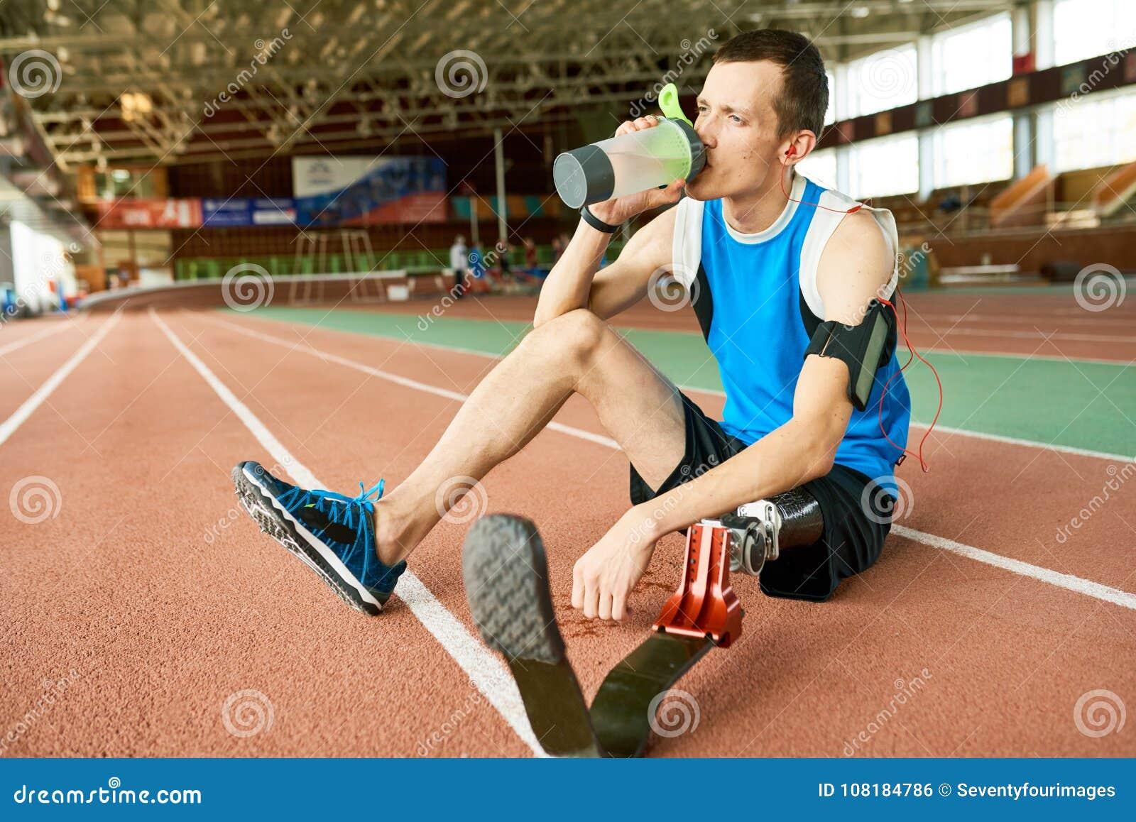 Amputee Sportsman Sitting on Stadium Track