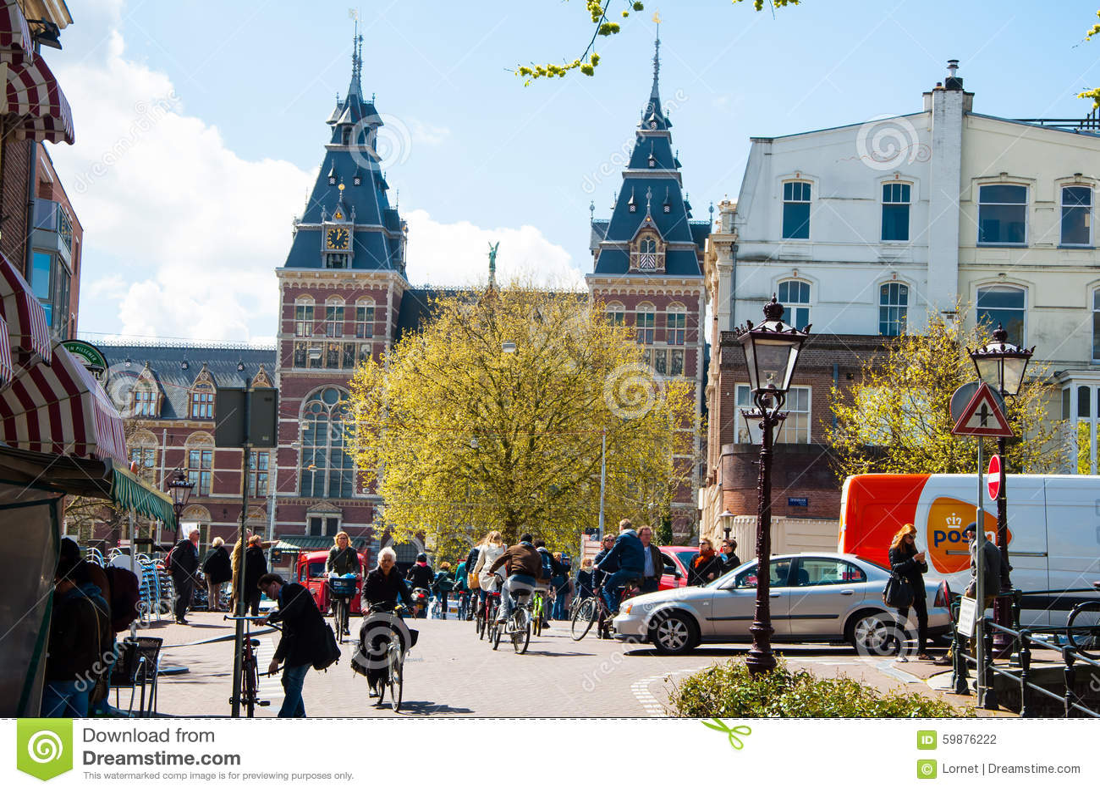 AMSTERDÃO 30 DE ABRIL: Os povos locais montam bicicletas na rua de Amsterdão, o Rijksmuseum são visíveis no fundo