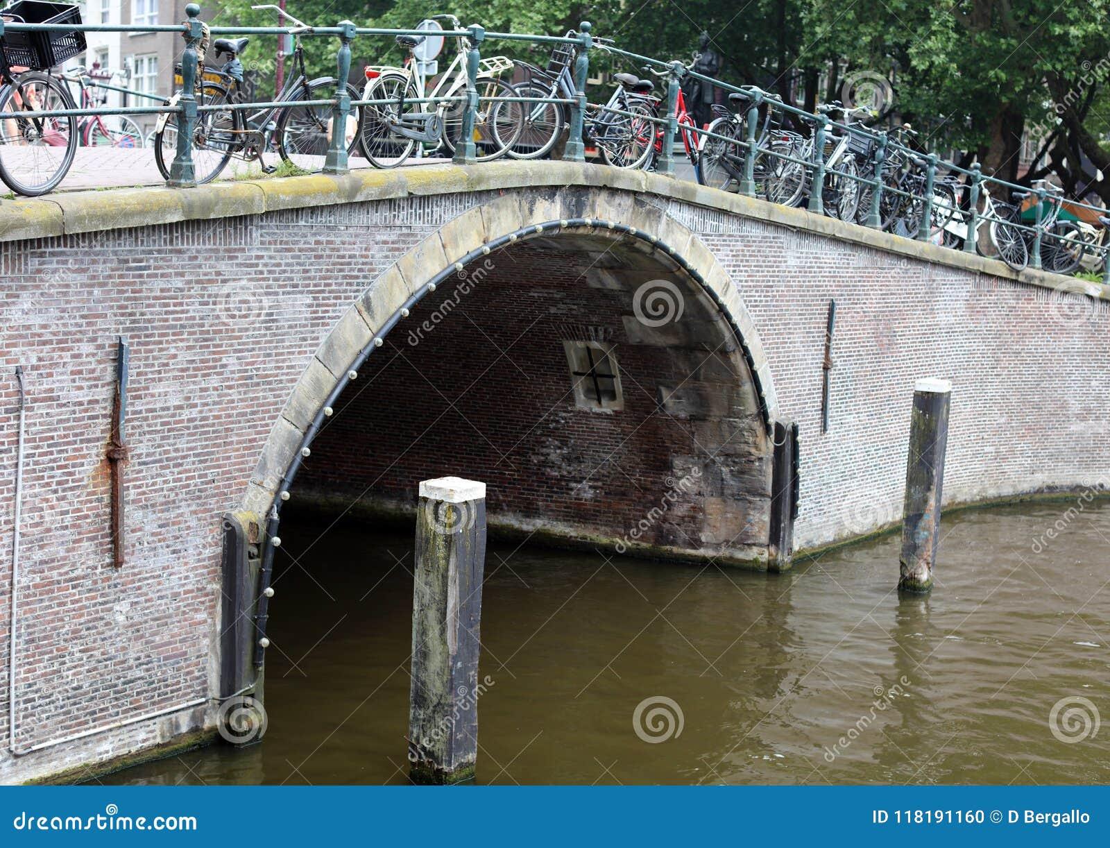 Amsterdão, os Países Baixos, canais da cidade, barcos, pontes e ruas Cidade europeia bonita e selvagem original
