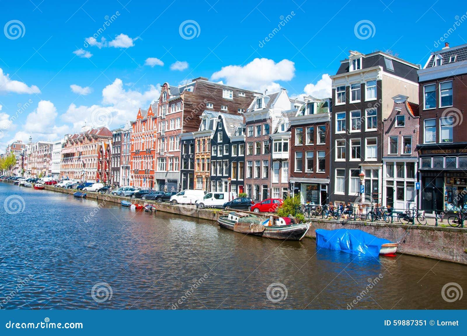 AMSTERDAM-APRIL 30: Amsterdam cityscape med rad av bilar, cyklar och fartyg som parkeras längs den Singel kanalen på April 30,201