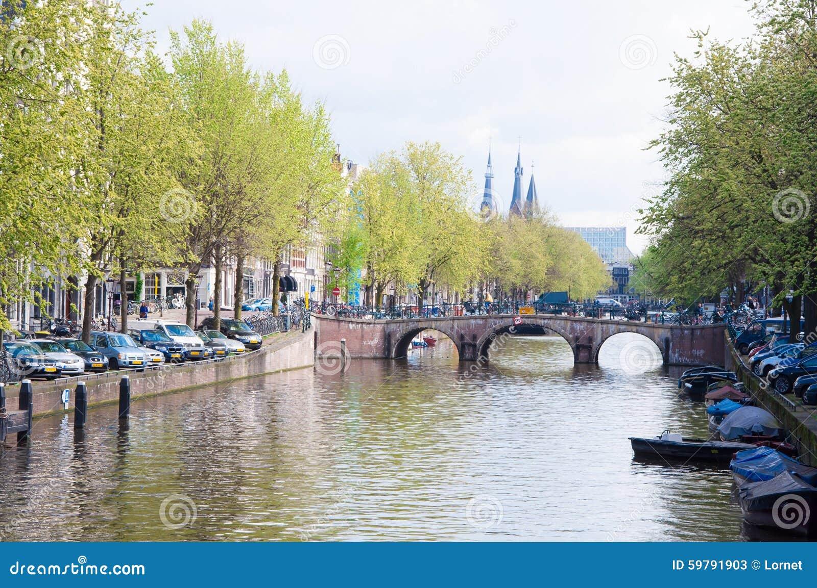 AMSTERDAM-APRIL 30: Amsterdam cityscape med rad av bilar som parkeras längs kanalen på April 30,2015, Nederländerna