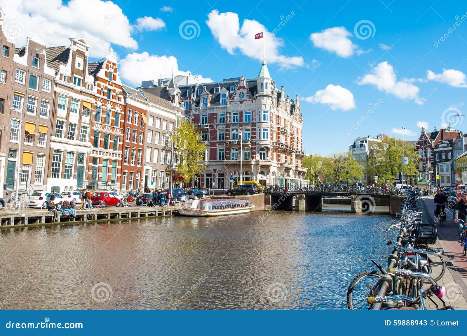 Amsterdam-April 30: Den Rokin kanalen med cyklar som parkeras längs banken, hotellet de l Europe, är synlig i bakgrunden