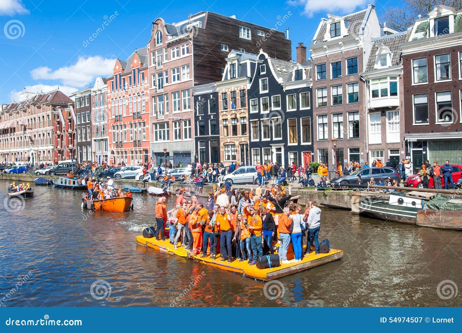 AMSTERDAM-APRIL 27: Det lyckliga folket firar konungens dag längs den Singel kanalen på den orange flotten, folkmassa tycker om f