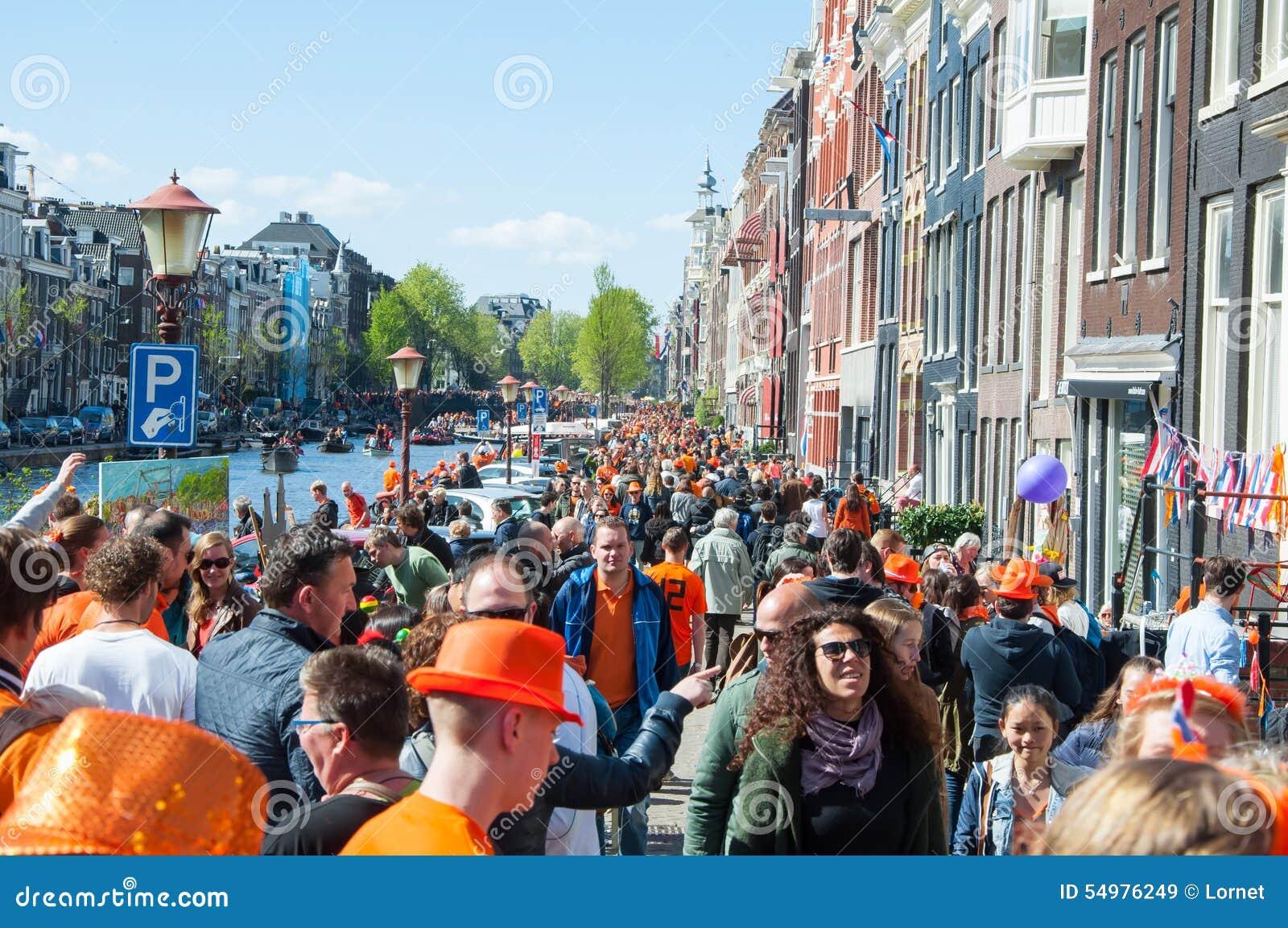 AMSTERDAM-APRIL 27: Lokaler och turister firar konungens dag längs banken av den Singel kanalen på April 27,2015, Nederländerna