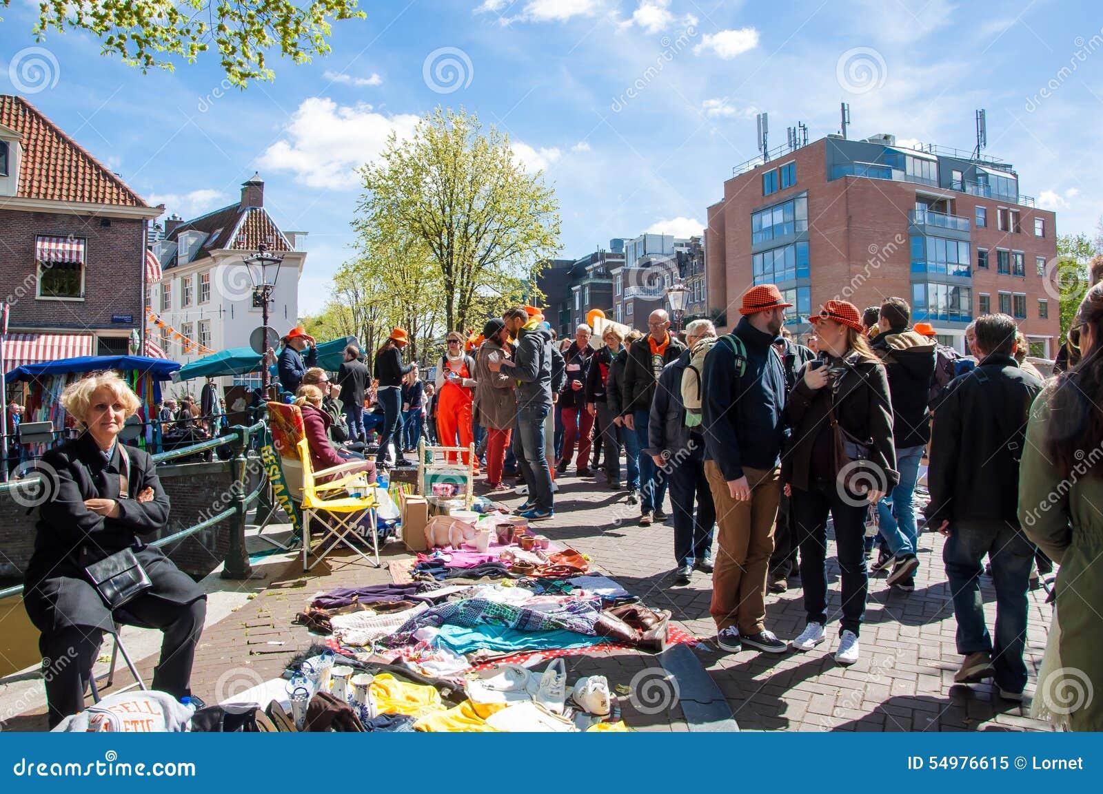 AMSTERDAM-APRIL 27: Lokaler visar deras gamla saker som är till salu i gammal mitt av Amsterdam på konungens dag på April 27, 201