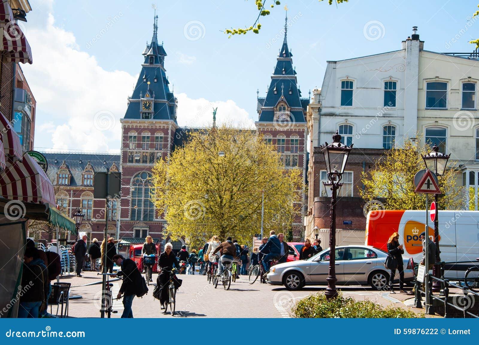 AMSTERDAM 30 DE ABRIL: La gente local monta las bicicletas en la calle de Amsterdam, el Rijksmuseum es visible en el fondo