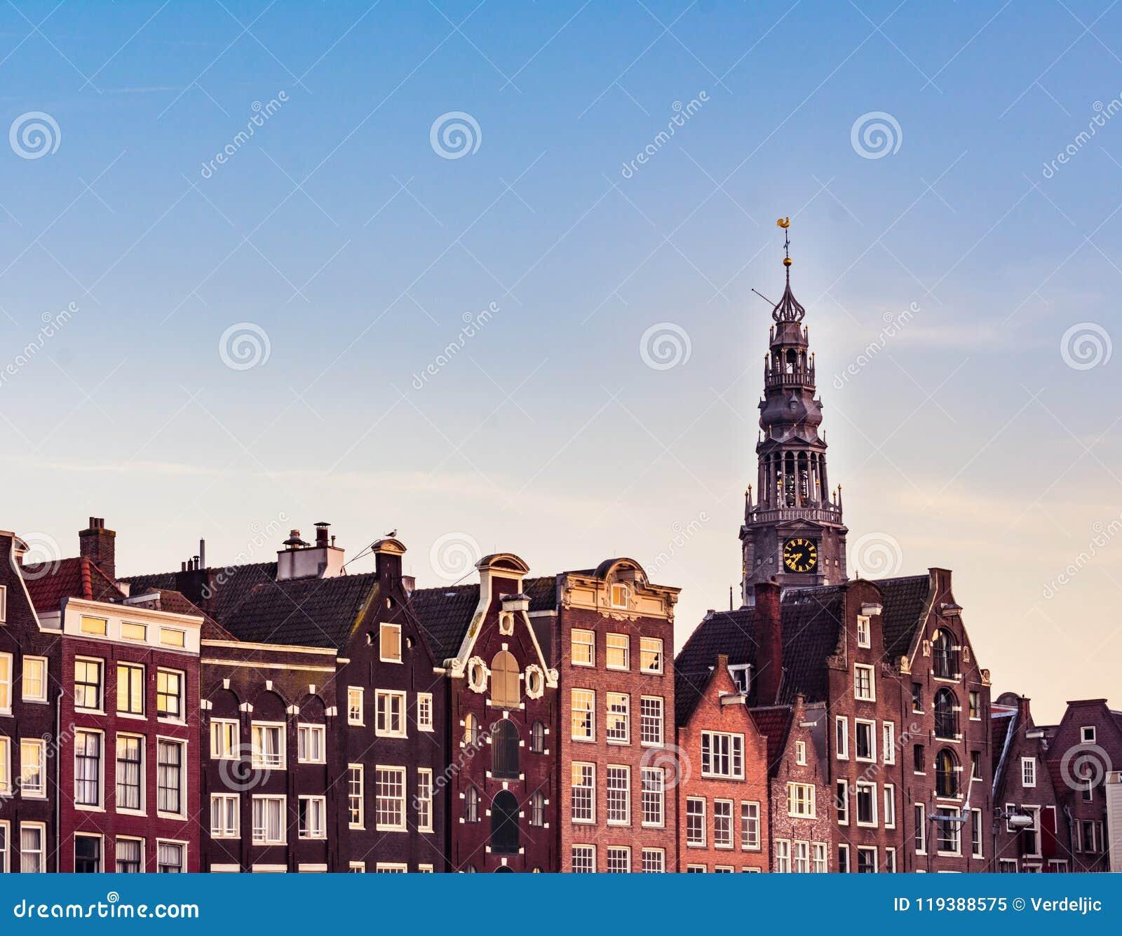 Amsterdam domy z kolorowymi fasadami i Westerkerk kościelny wierza podczas zmierzchu przy Amstel rzecznym kanałem w Amsterdam